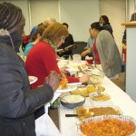 Guests and volunteers enjoy a holiday meal buffet