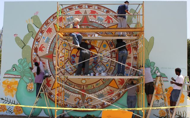 Volunteers paint a mural depicting an aztec calendar at for Aztec mural painting